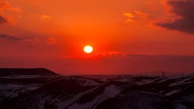 Timelapse from a sunset above the hills. Red sun goes down stock footage