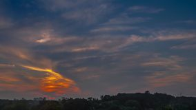 Sunset with clouds. Timelapse of sunset with clouds and high rise building silhouettes on horison stock video footage