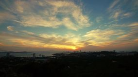 Timelapse sunset clouds,seaside urban skyline & forest. stock video footage