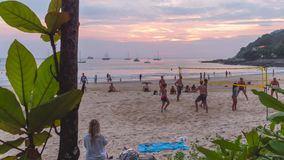 Timelapse: Tourists Playing Volleyball at Beautiful Tropical Naiharn Beach with Amazing Sunset. 4K. Phuket, Thailand -. 22 DEC 2017 stock footage