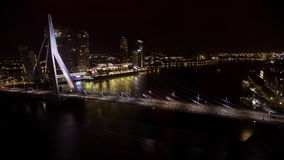 Timelapse of traffic on Erasmus Bridge at night, Rotterdam. Timelapse shot of car traffic on illuminated Erasmus Bridge and boats sailing down the river in stock video footage
