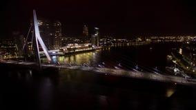 Timelapse of traffic on Erasmus Bridge at night, Rotterdam. Timelapse shot of car traffic on illuminated Erasmus Bridge and boats sailing down the river in stock video footage
