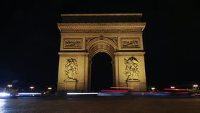 Timelapse of traffic near Triumphal Arch at night. Timelapse shot of car traffic by the Triumphal Arch of the Star illuminated at night. One of the most famous stock video