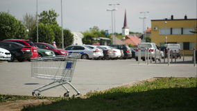 Timelapse of traffic on parking zone with empty. Timelapse of cars and people traffic on parking zone. Empty shopping cart standing in foreground stock footage