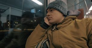 Timelapse of train passenger looking out the window during evening ride. Timelapse shot of a man in overclothes traveling by commuter train and looking out the stock footage