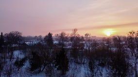 Timelapse, tramonto sopra la citt? innevata, profili scuri degli alberi nudi, i tetti delle case, il sole arancio di inverno archivi video