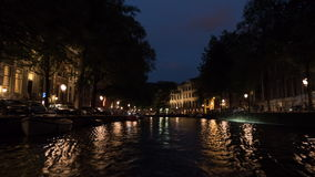 Timelapse of traveling on Amsterdam canals at night. Timelapse shot of sightseeing Amsterdam during tour on city canals at night, Netherlands stock video footage