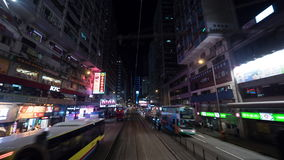 Timelapse of traveling through night Hong Kong by double-decker tram. HONG KONG - NOVEMBER 09, 2015: Timelapse shot of a ride by double-decker tram along the stock footage