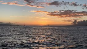 Timelapse of a Tropical Orange Sunset. A tropical, orange sunset is shown, with boats anchored in the distance, clouds moving, and a catamaran briefly entering stock video footage