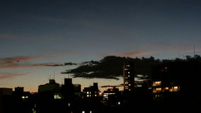 Timelapse of twilight cloudscape over the buildings. Timelapse of cloudscape over the skies of Tokyo buildings at twilight stock footage