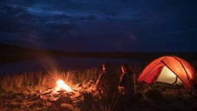 Timelapse unrecognisible пар вечером располагаться лагерем и пламя около пруда сток-видео