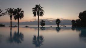Timelapse van avond bij de toevlucht Pool, palmen en scène met overzees en bergen stock video