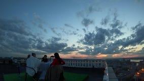 Timelapse van de hemel en de stad op achtergrond van mensen die uit op het dak hangen stock footage