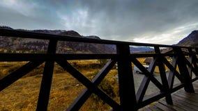 Timelapse van houten omheining op hoog terras bij berglandschap met wolken Horizontale schuifbeweging stock footage