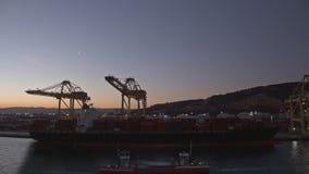 Timelapse van kranen die vrachtschip met containers laden bij industriële haven, Spanje stock footage