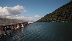 Timelapse van oude houten pijler in het overzees met bergen op backgorund stock video