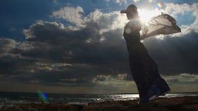 Timelapse van sterke vrouw alleen op kust, vrouwelijk silhouet, donkere bewolkte hemel stock videobeelden