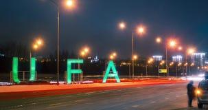 Timelapse van teken Oefa en vervoerverkeer bij de hoofdweg in stad in de de winternacht Bashkortostan, Rusland stock footage
