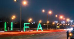 Timelapse van teken Oefa en vervoerverkeer bij de hoofdweg in stad in de de winternacht Bashkortostan, Rusland stock videobeelden