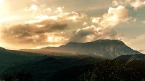 Timelapse variopinto di tramonto sopra il paesaggio della montagna Nuvole commoventi con luce drammatica stock footage