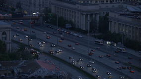 Timelapse. Very intense traffic on the streets of the city. In evening time. Wide road. View from the top point. stock footage