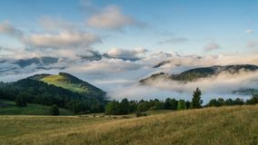 Peaceful foggy morning with clouds moving over beutiful landscape in mountains. Time lapse Zoom in stock footage