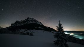 Night sky with stars moving over mountain peak in winter astronomy time lapse. Timelapse video of starry night sky with stars rotating over snowy mountain peak stock video footage
