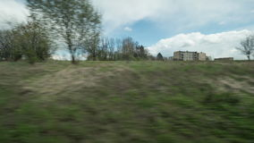 Timelapse view from riding train window of coutryside landscape, trees, forests, houses against cloudy sky stock video