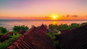 Timelapse view sunrise the background of the ocean and roof bungalows with tropical trees in Amed on the island of Bali stock video footage