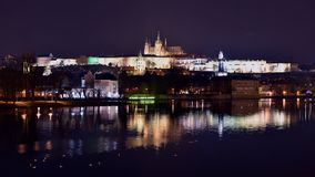 Timelapse of vltava river at charles bridge and prague castle at night with reflections. Czech republic stock video footage