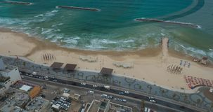 Timelapse of waves, car and people traffic on sea-front. Tel Aviv, Israel. Timelapse shot of car traffic on waterfront road and sea waves washing the shore. City stock footage