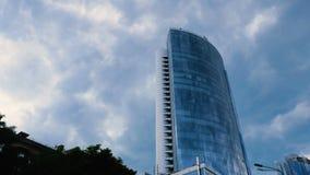 Timelapse wideo Widok na wielkim szklanym centrum biznesu przeciw tłu poruszające szare chmury spod spodu zdjęcie wideo
