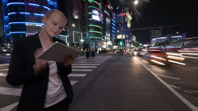 Timelapse of woman with tablet PC in night Seoul, South Korea. Timelapse panning and wide angle shot of young woman using touch pad on the busy street of night stock video footage