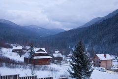 Timelapse of wooden cottages in mountain village valley surrounded with coniferous forest and snowy mountains. Fast view stock video