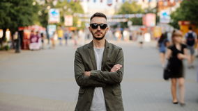 Timelapse of Young man in sunglasses standing still at sidewalk in crowd traffic stream with people moving fast stock video