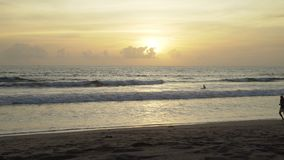 Timelapsezonsondergang op het strand in Bali Gesilhouetteerde Mensen stock video