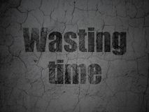 Timeline concept: Wasting Time on grunge wall background. Timeline concept: Black Wasting Time on grunge textured concrete wall background Royalty Free Stock Photography