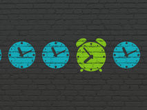 Timeline concept: green alarm clock icon on wall Stock Images