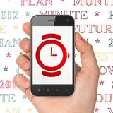 Timeline concept: Hand Holding Smartphone with Hand Watch on display. Timeline concept: Hand Holding Smartphone with  red Hand Watch icon on display,  Tag Cloud Royalty Free Stock Photography