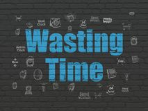Timeline concept: Wasting Time on wall background. Timeline concept: Painted blue text Wasting Time on Black Brick wall background with  Hand Drawing Time Icons Stock Photo