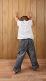 When Timeouts don't work. A young boy stands with his hands on the wall in a pose of being arrested Stock Images