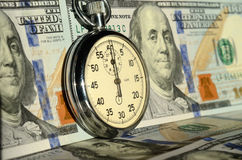 The timer on the background of dollar bills (advantages and disa Royalty Free Stock Image