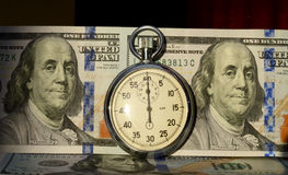 The timer on the background of dollar bills (time - money, incom Royalty Free Stock Photos