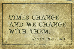 Times change LP. Times change and we  -  ancient Latin proverb printed on grunge vintage cardboard Stock Photos