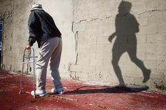 Times gone by. An older disabled man reflects on the wall and the days of his running youth
