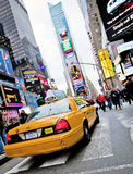 Times square. NEW YORK - DECEMBER 17: Yellow cab speeds through Times Square the busy tourist intersection of neon art and commerce and is an iconic street of royalty free stock photography