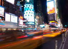 Times square cabs passing by. A night shot of times square with light streaks stock photos