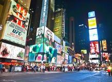 Times Square con las porciones de visitantes en la noche en New York City Imágenes de archivo libres de regalías