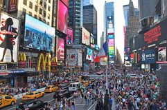 The worlds famous Times Square in New York City day time. Times Square is a major commercial intersection, tourist destination, entertainment center and stock photo