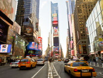 Times Square, New York City. Famous landmarks and yellow taxis on Times Square in New York City with neon lights and tall buildings on a sunny winters afternoon stock images